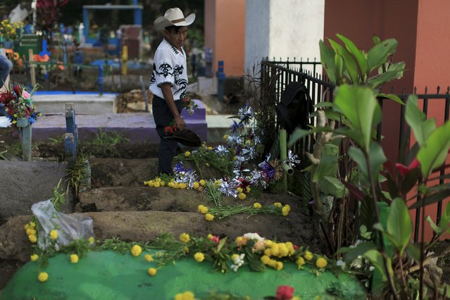 A man decorates the grave of a relative during celebration of the Day of the Dead in Nahuizalco, El Salvador November 2, 2015. Salvadorans mark the Day of the Dead by paying homage to their dead relatives, by cleaning and decorating their graves. (Photo by Jose Cabezas/Reuters)