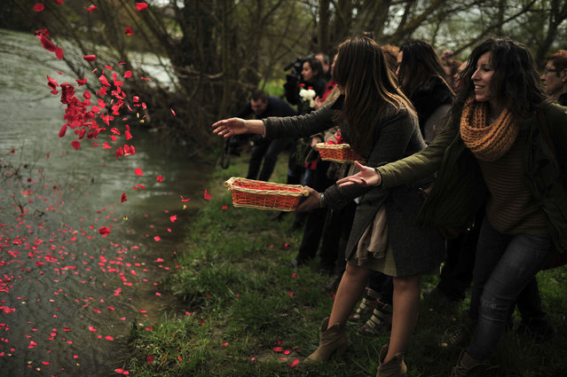 Female gypsy people throw flower petals into the Arga River in honor of their ancestors on the Day of the Gypsy, in Pamplona northern Spain, on Monday, April 8, 2013. (Photo by Alvaro Barrientos/AP Photo)