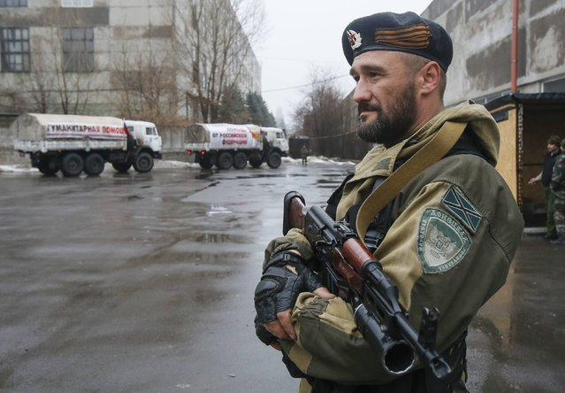 A pro-Russian-separatist patrols the street in front of Russian humanitarian trucks in Makiivka (Makeyevka) in Donetsk region, December 12, 2014. According to Russian media, over 50 trucks arrived in Donetsk while another 80 trucks arrived in Luhansk. (Photo by Maxim Shemetov/Reuters)