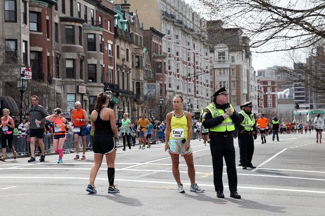 Police and runners stand near Kenmore Square after two bombs exploded during the 117th Boston Marathon on April 15, 2013 in Boston, Massachusetts. (Photo by Alex Trautwig)