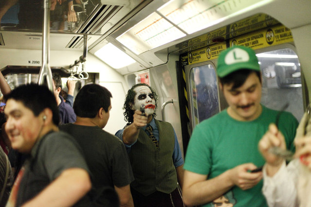 In this October 31, 2014 file photo, a man dressed as DC Comics super villain The Joker points a toy gun as he strikes a pose in a subway car in Santiago, Chile. (Photo by Luis Hidalgo/AP Photo)