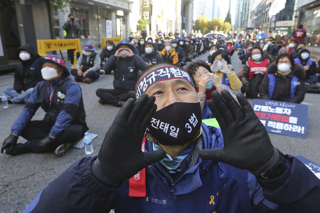 """Temporary workers wearing face masks to help protect against the spread of the coronavirus shout during a rally to demand better working conditions in Seoul, South Korea, Tuesday, November 10 , 2020. The sign on headband read """"Elimination of temporary workers"""". (Photo by Ahn Young-joon/AP Photo)"""