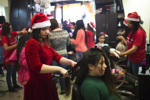 A Palestinian hairstylist wearing a Santa Claus hat straightens the hair of a customer in a salon at Jerusalem's Old City December 19, 2014. (Photo by Amir Cohen/Reuters)