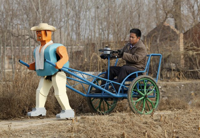 Farmer Wu Yulu drives his rickshaw pulled by a his self-made walking robot near his home in a village at the outskirts of Beijing January 8, 2009. This robot is the latest and largest development of hobby inventor Wu, who started to build robots in 1986, made of wire, metal, screws and nails found in rubbish sites. (Photo by Reinhard Krause/Reuters)