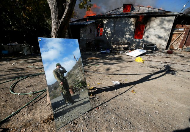 A man is reflected in a mirror as he stands near a house set on fire by departing ethnic Armenians, in an area which had held under their military control but is soon to be turned over to Azerbaijan, in the village of Cherektar in the region of Nagorno-Karabakh, November 14, 2020. (Photo by Reuters/Stringer)