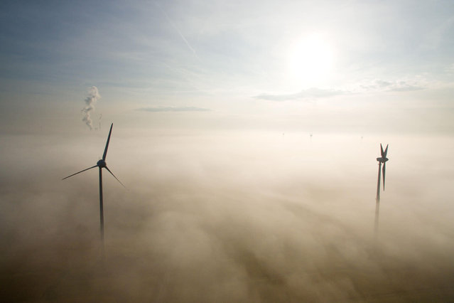 Windmills are seen through the morning mist rising from a field in Sehnde near Hanover, northern Germany, on September 22, 2016. Autumn officially begins on the equinox on September 22. (Photo by Julian Stratenschulte/AFP Photo/DPA)