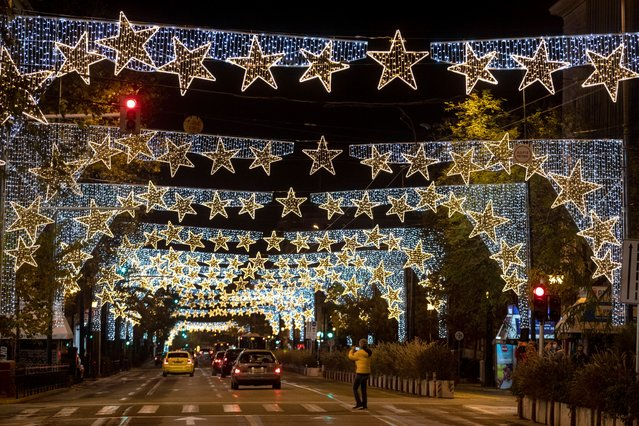 A man crosses a central street which is decorated for Christmas, in Athens, Greece, Saturday, December 12, 2020. The government said it will maintain core lockdown measures through the Christmas holidays, acknowledging that month long restrictions have not reduced COVID-19 cases to the extent it had hoped for. (Photo by Yorgos Karahalis/AP Photo)