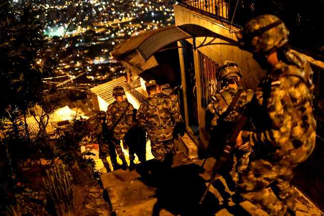 Soldiers patrol the alleys of the Comuna 13 neighbourhood in Medellin, Antioquia Department, Colombia, on April 27, 2018. The Comuna 13 neighbourhood was militarized after gang violence increased following the arrest on April 21 of several gang leaders, including that of Cristian Camilo Mazo Castaneda, aka Sombra, leader of the Robledo gang. (Photo by Joaquin Sarmiento/AFP Photo)