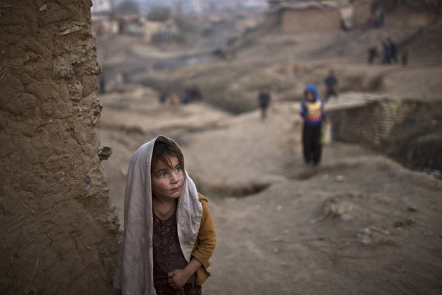 Afghan refugee Sayma Naseeb, 4, stands by the doorway of her family's mud house in a poor neighborhood on the outskirts of Islamabad, Pakistan, Sunday, December 28, 2014. (Photo by Muhammed Muheisen/AP Photo)