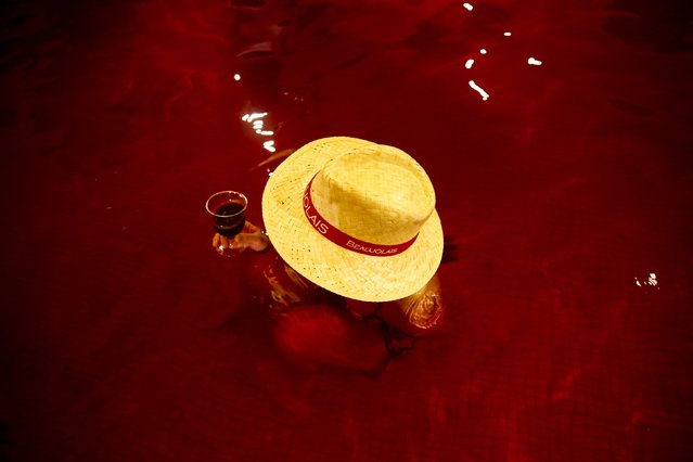 A woman drinks wine in a hot bath with coloured water representing wine at the Hakone Kowaki-en Yunessun spa resort during an event marking Beaujolais Nouveau Day in Hakone west of Tokyo, November 19, 2015. (Photo by Thomas Peter/Reuters)