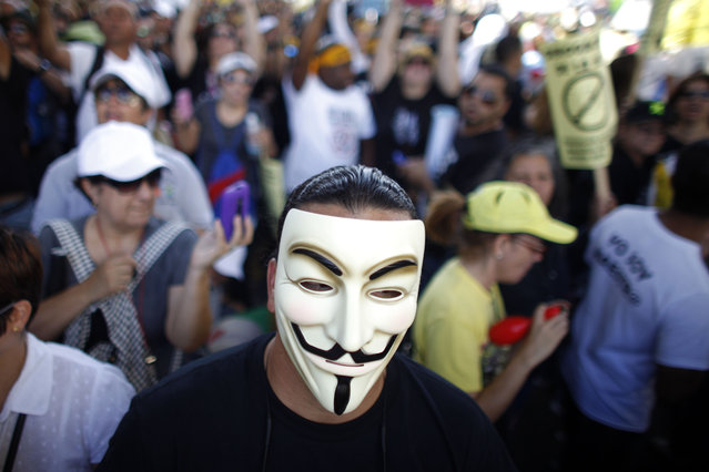 Puerto Rico: A demonstrator wearing a Guy Fawkes mask joins a teacher's protest outside the Department of Labor in San Juan, Puerto Rico, Wednesday, January 15, 2014. (Photo by Ricardo Arduengo/AP Photo)