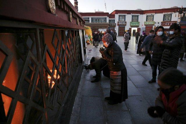 Pilgrims pray outside the Jokhang Temple in central Lhasa, Tibet Autonomous Region, China, at dawn November 20, 2015. (Photo by Damir Sagolj/Reuters)