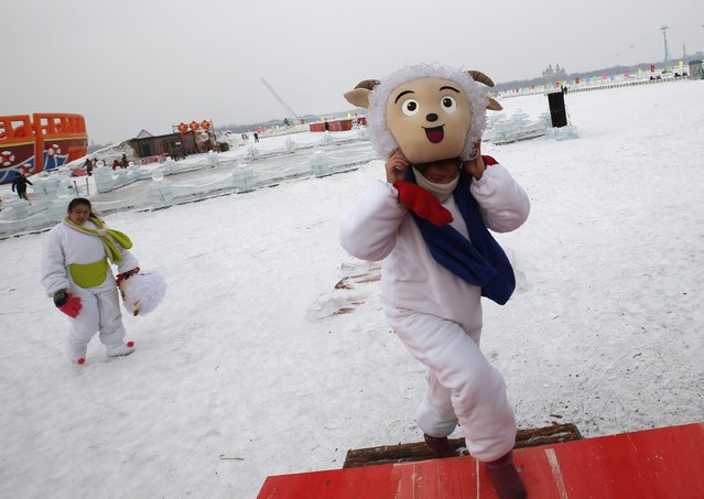 Dancers in costumes symbolizing sheep leave after finishing their performance to celebrate the Harbin International Ice and Snow Sculpture Festival at the Songhua River in the northern city of Harbin, Heilongjiang province January 5, 2015. (Photo by Kim Kyung-Hoon/Reuters)