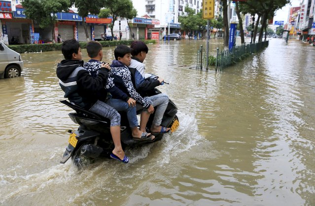 Residents ride a motorcycle along a flooded street after heavy rainfall in Hezhou, Guangxi Zhuang Autonomous Region, China, November 14, 2015. (Photo by Reuters/Stringer)
