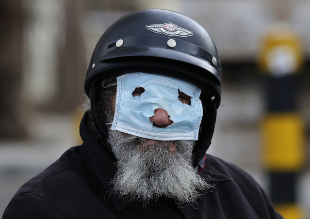 A man with a motorcycle helmet covers his face with a mask, as he watches municipal policemen order people to leave the corniche, or waterfront promenade, along the Mediterranean Sea, as the country's top security council and the government were meeting over the spread of coronavirus, in Beirut, Lebanon, Sunday, March 15, 2020. (Photo by Hussein Malla/AP Photo)
