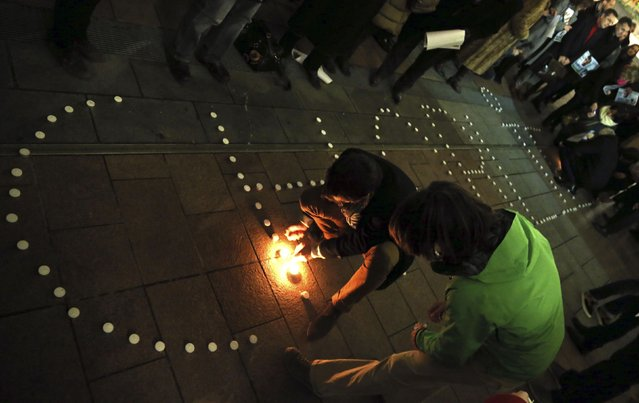 "People try to light candles to form the word ""Charlie"" to pay tribute to the victims of a shooting by gunmen at the offices of weekly satirical magazine Charlie Hebdo in Paris, in front of the European Parliament in Brussels January 7, 2015. Gunmen stormed the Paris offices of the weekly satirical magazine Charlie Hebdo, renowned for lampooning radical Islam. (Photo by Francois Lenoir/Reuters)"