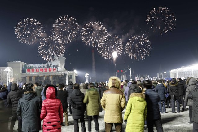 A fireworks display decorates the night sky to celebrate the New Year, as crowds of people look on, at Kim Il Sung Square in Pyongyang, North Korea, early Friday, January, 1, 2021. (Photo by Jon Chol Jin/AP Photo)