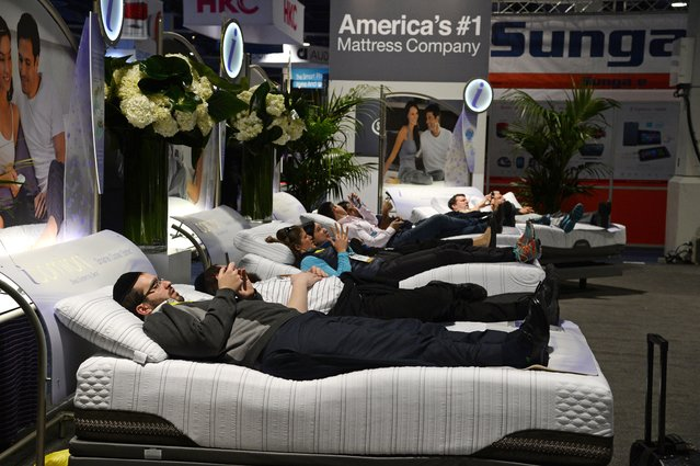 Attendees lay on Serta mattresses at the Serta stand, January 6, 2015 at the Consumer Electronics Show in Las Vegas, Nevada. (Photo by Robyn Beck/AFP Photo)