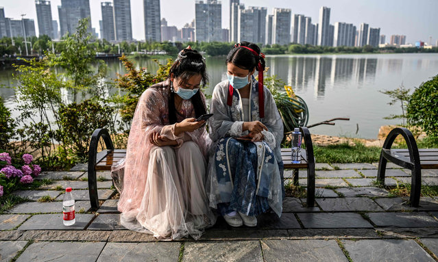 "Young women wearing facemasks and traditional costumes of Song dynasty and Tang dynasty are seated on a bench in a park next to the East Lake in Wuhan, in China's central Hubei province on May 17, 2020. The Guardian picture desk has chosen on December 17, 2020, the AFP photojournalist Hector Retamal as ""Agency Photographer of the Year 2020"" for his coverage of the novel coronavirus Covid-19 pandemic in Wuhan, China. (Photo by Hector Retamal/AFP Photo)"