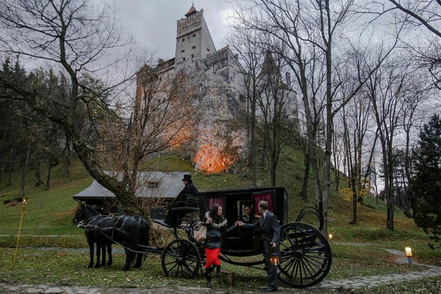 Tami Varma is helped out of a horse-drawn carriage by guide near the northern facade of the Bran Castle, in Brasov county, Romania, October 31, 2016. (Photo by Octav Ganea/Reuters/Inquam Photos)
