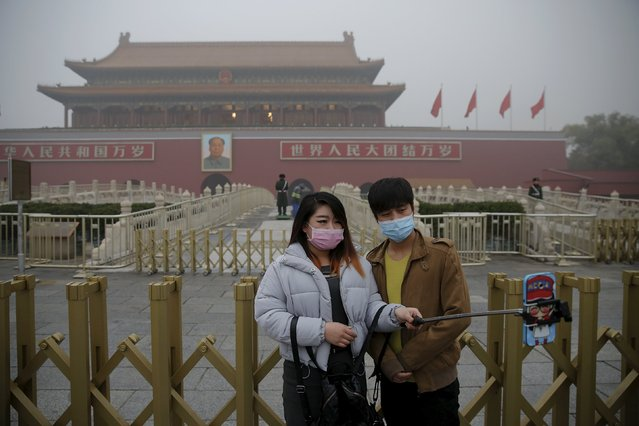 A couple wearing protective masks take pictures of themselves at the Tiananmen Gate on an extremely polluted day as hazardous, choking smog continues to blanket Beijing, China December 1, 2015. (Photo by Damir Sagolj/Reuters)