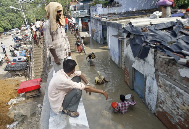 Residents carry their belongings through an alley flooded with the rising water level of river Yamuna after heavy monsoon rains in New Delhi June 19, 2013. The rains are at least twice as heavy as usual in northwest and central India as the June-September monsoon spreads north, covering the whole country a month faster than normal. (Photo by Anindito Mukherjee/Reuters)