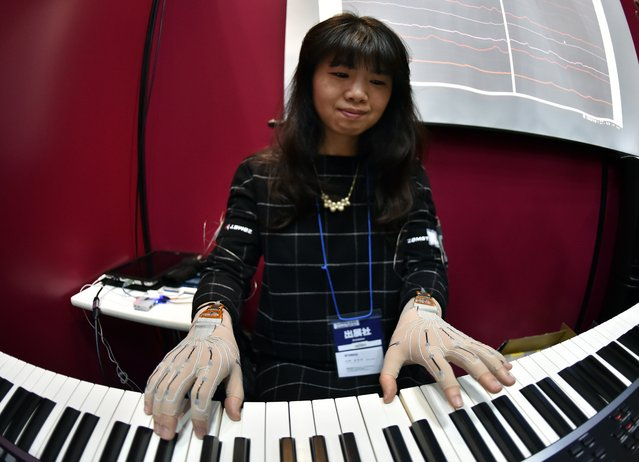 A pianist wears special gloves with motion sensors and plays a keyboard to record fingerwork at the Wearable Device Technology Expo in Tokyo on January 14, 2015. Japanese music instruments maker Yamaha developed the gloves with 12 sensors of frexible nanomaterial consisting of aligned carbon nano tubes to monitor players' fingering. (Photo by Yoshikazu Tsuno/AFP Photo)