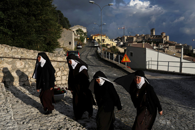Nuns walk up to the entrance of a church in Castel del Monte, in the province of L'Aquila in Abruzzo, inside the national park of the Gran Sasso e Monti della Laga, Italy, September 8, 2016. (Photo by Siegfried Modola/Reuters)