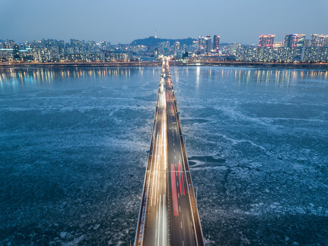A photo taken on January 10, 2021 shows a general view of traffic passing over a bridge above the frozen Han river, before the Seoul city skyline. (Photo by Ed Jones/AFP Photo)