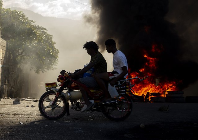 Men ride a motorcycle past a burning barricade during a protest to demand the resignation of Haitian President Jovenel Moise in Port-au-Prince, Haiti, Sunday, February 7, 2021. (Photo by Dieu Nalio Chery/AP Photo)
