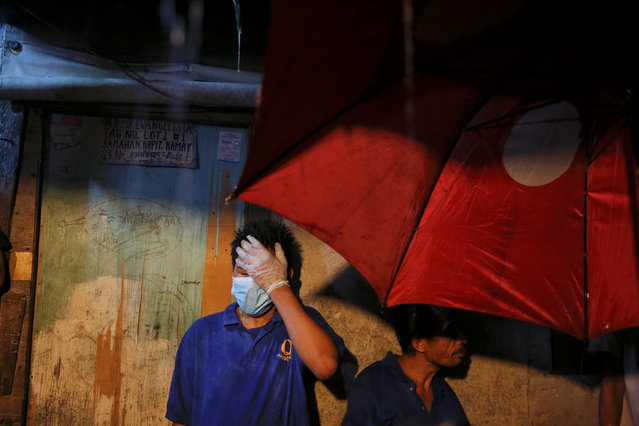 Funeral parlour workers wait to take bodies out of a house in Manila, Philippines early November 1, 2016. (Photo by Damir Sagolj/Reuters)
