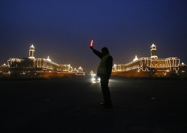 A traffic policeman signals traffic to stop near the Indian Defence Ministry (L) and Home Ministry buildings, which are lit up ahead of the country's Republic Day celebrations in New Delhi January 20, 2015. (Photo by Anindito Mukherjee/Reuters)