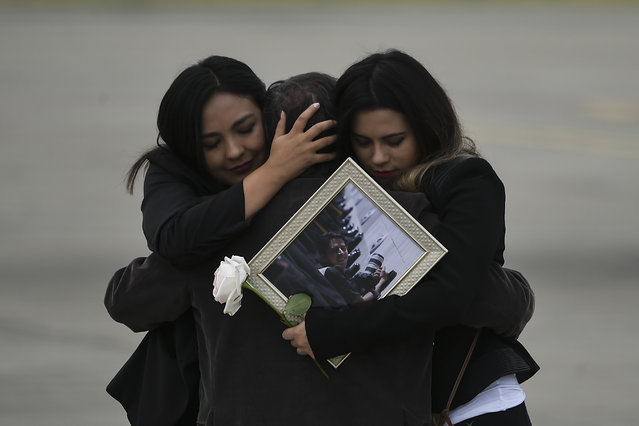 Relatives of the slain members of the news team from Ecuadorean newspaper El Comercio, embrace as the coffins containing the remains of their loved ones are carried onto an airplane of the Ecuadorean Air Force to be flown to Quito, at the Alfonso Bonilla Aragon airport in Palmira, Colombia, on June 27, 2018. The trio -journalist Javier Ortega, photographer Paul Rivas and driver Efrain Segarra- had been kidnapped and slain while covering a story on violence along the remote border with Colombia prompting both countries to send troops to hunt down the perpetrators. (Photo by Luis Robayo/AFP Photo)
