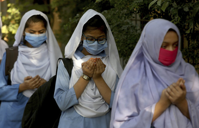 Students wearing face masks to prevent the spread of the coronavirus as they pray upon their arrival at their school, in Karachi, Pakistan, Monday, January 18, 2021. Pakistani authorities started to reopen schools in phases despite a steady increase in deaths and infections from the coronavirus, official said. (Photo by Fareed Khan/AP Photo)