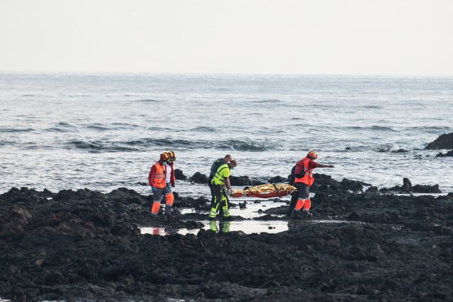 Members of the emergency services transfer a body as they continue the search of missing migrants after 27 migrants were rescued after their small fishing boat sank off the coast in Lanzarote, Canary Islands, Spain, 25 November 2020. A total of 27 people have been rescued alive while eight bodies have been found from the group of 37 migrants that are believed were traveling on board the fishing boat. Rescue services continue searching the area. (Photo by Javier Fuentes Figueroa/EPA/EFE)