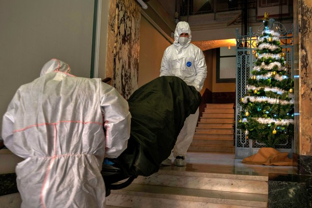 Mortuary workers walk past a Christmas tree as they remove the body of an elderly person who died of COVID-19 from a nursing home in downtown Barcelona, Spain, Wednesday, December 23, 2020. (Photo by Emilio Morenatti/AP Photo)