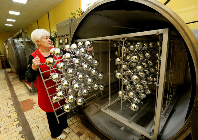 """An employee unloads glass spheres covered with a metal layer from vacuum chamber, for Christmas and New Year decorations at the """"Biryusinka"""" toy factory, which has been producing decorations and toys for the festive season since 1942, in the Siberian city of Krasnoyarsk, Russia, November 16, 2016. (Photo by Ilya Naymushin/Reuters)"""