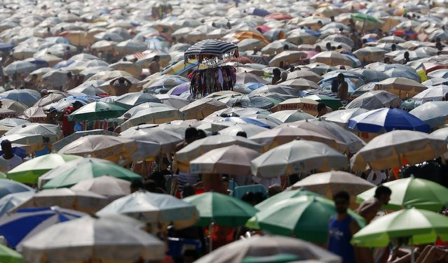 Bikinis for sale are pictured atop parasols of people gathering on Ipanema beach in Rio de Janeiro December 30, 2014. (Photo by Ricardo Moraes/Reuters)