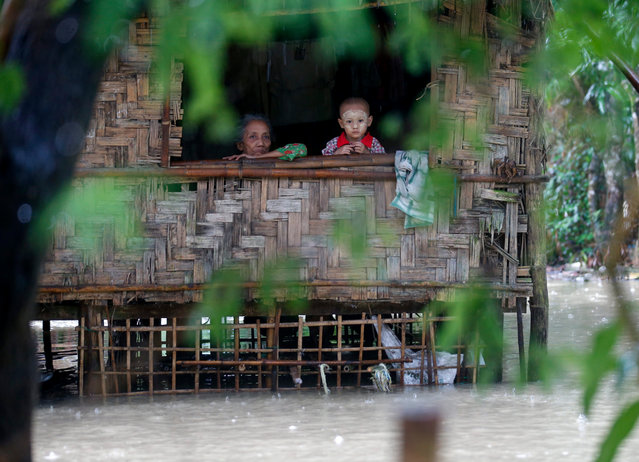 An elderly person and a child look outside from a window of a partially flooded house at Kyein Chaung village of Kangyee Daunk township in the Ayeyarwady Region, Myanmar, 12 August 2016. According to Myanmar state media on 10 August 2016, more than 300,000 people were affected by flooding that submerged a total of 703 villages, forcing 38,000 to take refuge in over 180 local shelters in the Ayeyarwady Region. (Photo by Lynn Bo Bo/EPA)