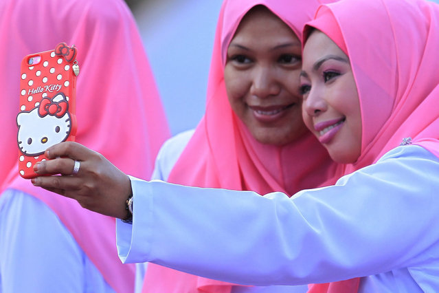 Members of the United Malays National Organisation (UMNO), take a selfie during the opening ceremony of Malaysia's ruling party UMNO 69th General Assembly in Kuala Lumpur, Malaysia, 10 December 2015. (Photo by Fazry Ismail/EPA)