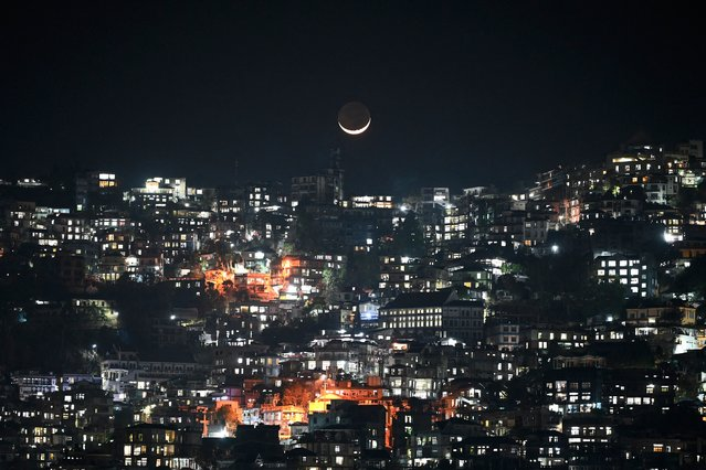 A general view shows a crescent moon over homes on a hillside in Aizawl, the capital of the northeastern Indian state of Mizoram on March 16, 2021. (Photo by Sajjad Hussain/AFP Photo)