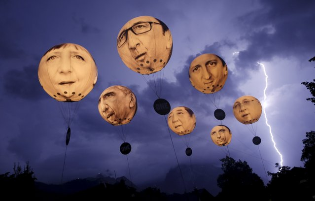 "Lightning strikes the Alpine mountains over Garmisch-Partenkirchen as balloons, made by the ""ONE"" campaigning organisation, depicting leaders of the G7 countries are inflated in Garmisch-Partenkirchen June 7, 2015. (Photo by Wolfgang Rattay/Reuters)"