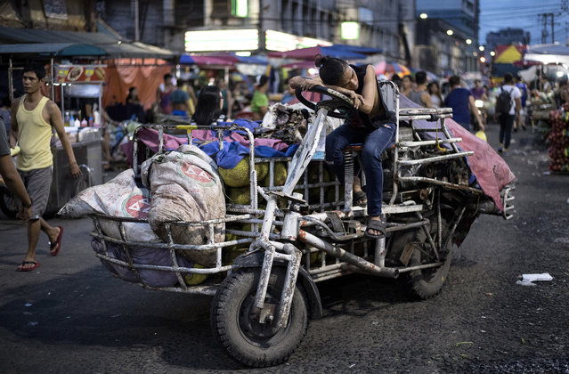 A worker who delivers vegetables rests on a rickshaw at Divisoria Market in Manila, Philippines on July 12, 2018. (Photo by Noel Celis/AFP Photo)