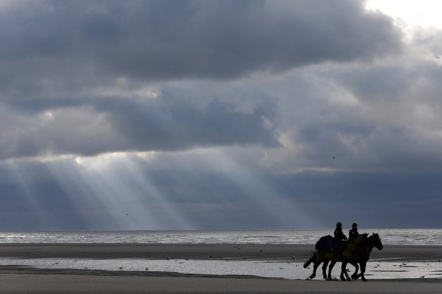 """French mounted police officers patrol on the beach during the """"Quaduro"""" endurance race in Le Touquet January 31, 2015. (Photo by Pascal Rossignol/Reuters)"""