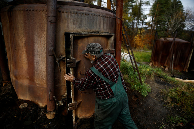 Charcoal burner Zygmunt Furdygiel closes a charcoal furnace full of wood at a charcoal making site in the forest of Bieszczady Mountains, near the village of Baligrod, Poland October 27, 2016. (Photo by Kacper Pempel/Reuters)