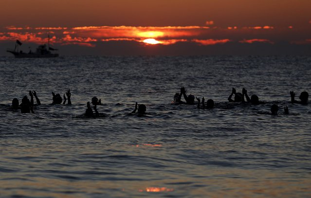 Local swimmers pray to the sun during sunrise to wish for calm waters and good fortune in the new year in Odawara, Kanagawa prefecture, west of Tokyo, Japan, January 1, 2016. (Photo by Yuya Shino/Reuters)
