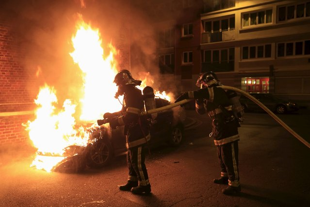 Firefighters extinguish a burning car following New Year celebrations in Lille, northern France, January 1, 2016. (Photo by Pascal Rossignol/Reuters)