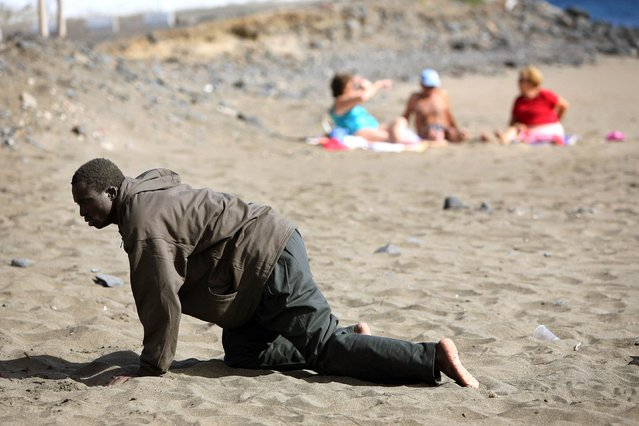 A would-be immigrant crawls on the beach after his arrival on a makeshift boat on the Gran Tarajal beach in Spain's Canary Island of Fuerteventura in this May 5, 2006 file photo.  (Photo by Juan Medina/Reuters)