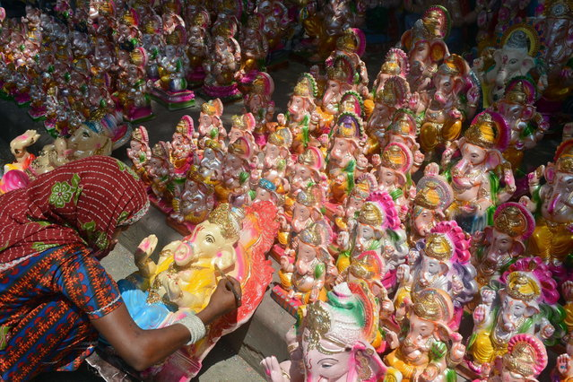 An Indian artisan decorates an idol of Hindu god Lord Ganesh at a roadside market ahead of the Ganesh Chaturthi festival in New Delhi on September 7, 2013. The Hindu festival which celebrates the rebirth of the God Lord Ganesha, begins this year on September 9 and culminates on September 19, with many of the statues being immersed in bodies of water. (Photo by AFP Photo/Raveendran)