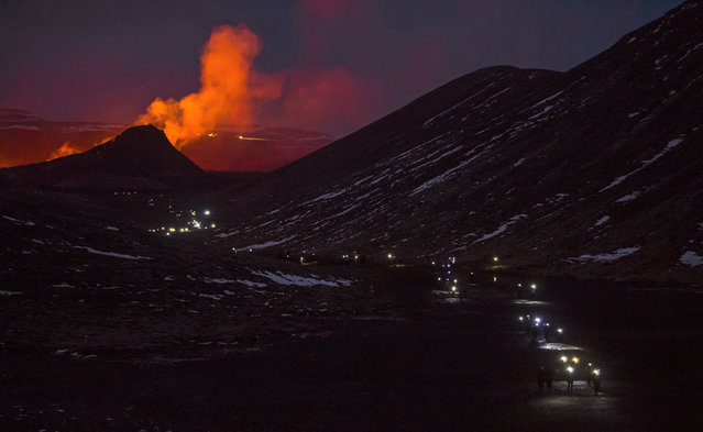 People use flashlights as they take the pathway down after watching the Lava flows from an eruption of a volcano on the Reykjanes Peninsula in southwestern Iceland on Wednesday, March 31, 2021. Iceland's latest volcano eruption is still attracting crowds of people hoping to get close to the gentle lava flows. (Photo by Marco Di Marco/AP Photo)